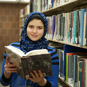 student in library holding book